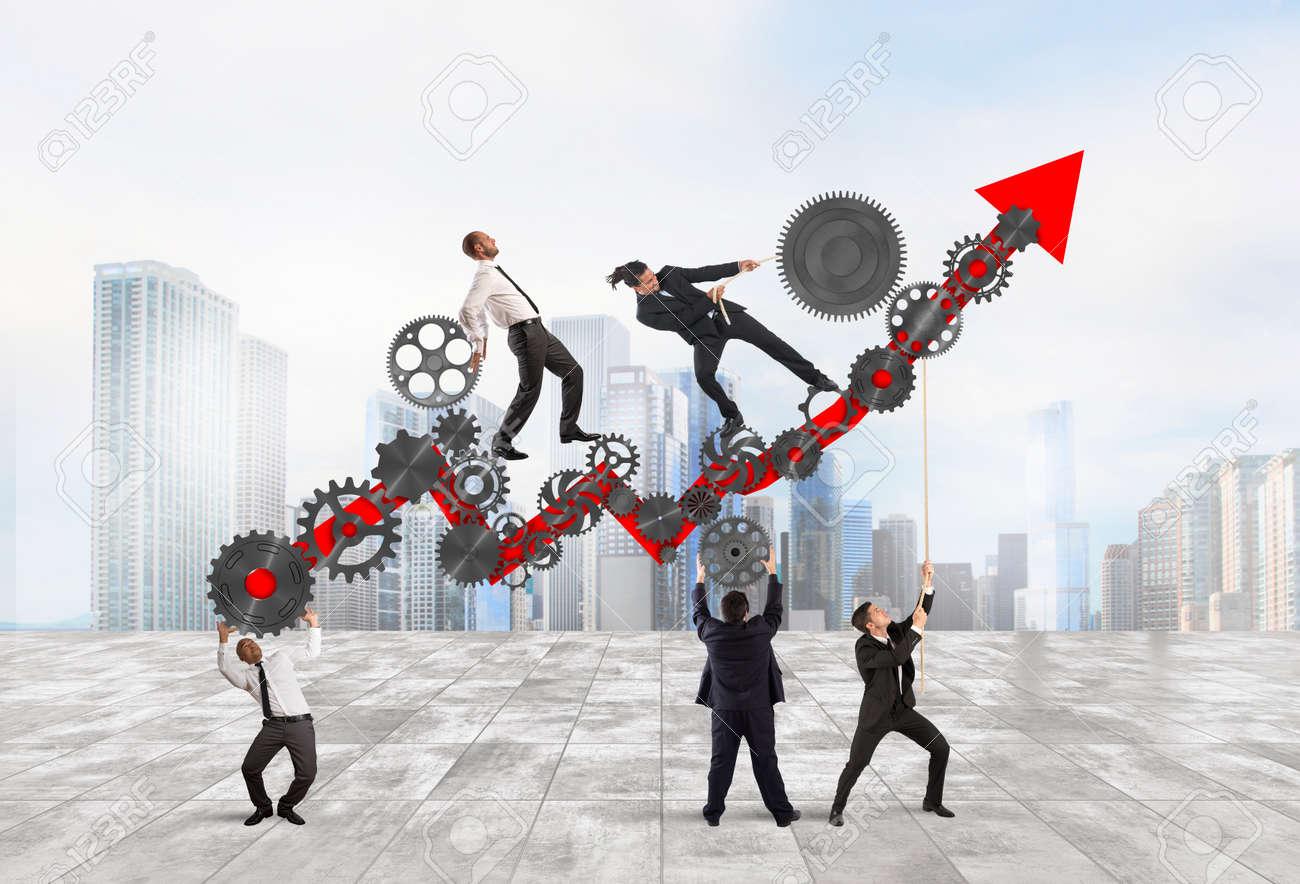 Teamwork build an arrow upwards with gears mechanism Standard-Bild - 63888850