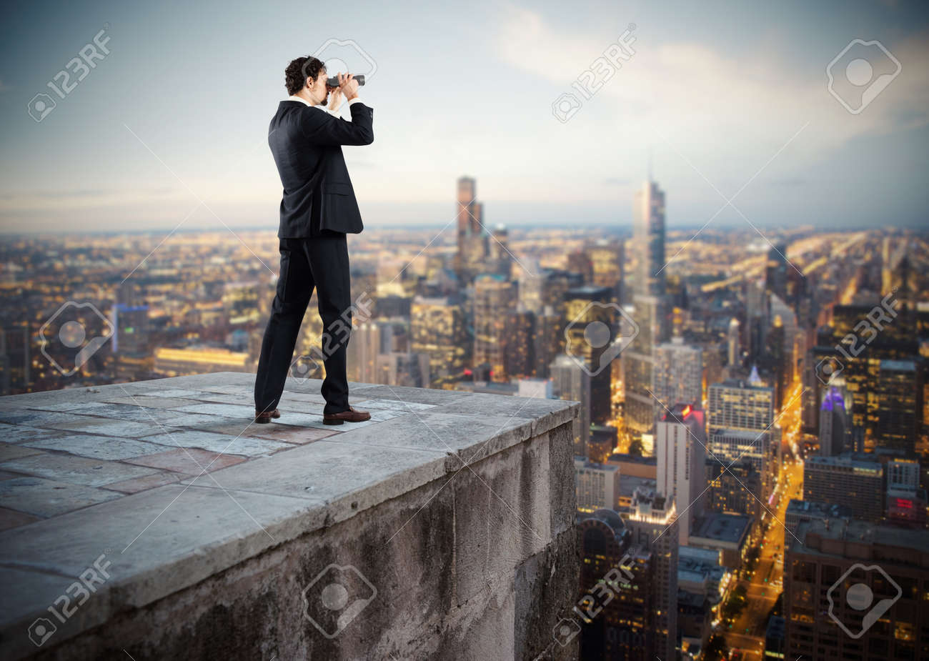 Businessman looks at the city from the roof with binoculars - 63888858