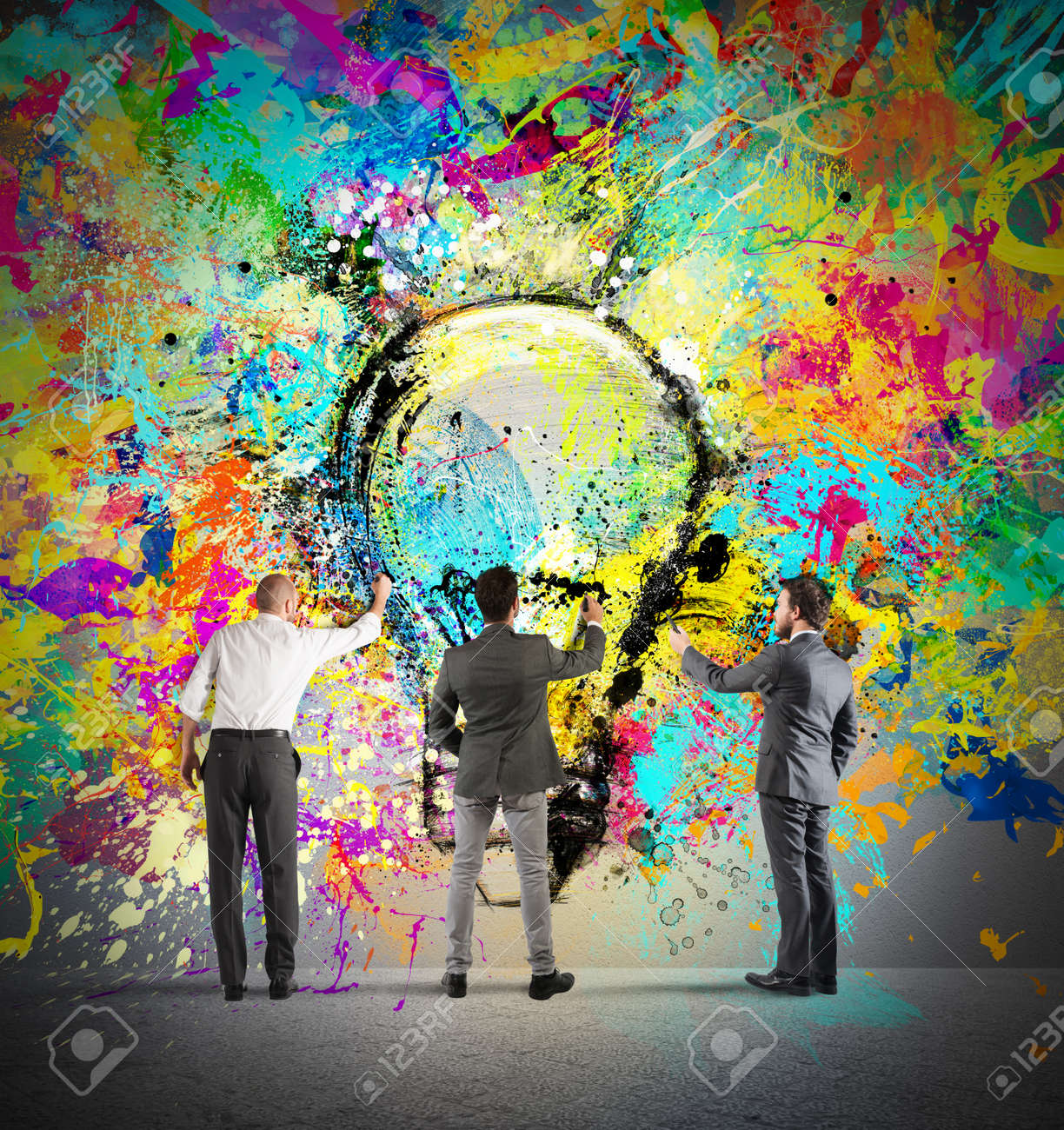 Business person paint together a big colored lightbulb on the wall - 63888862