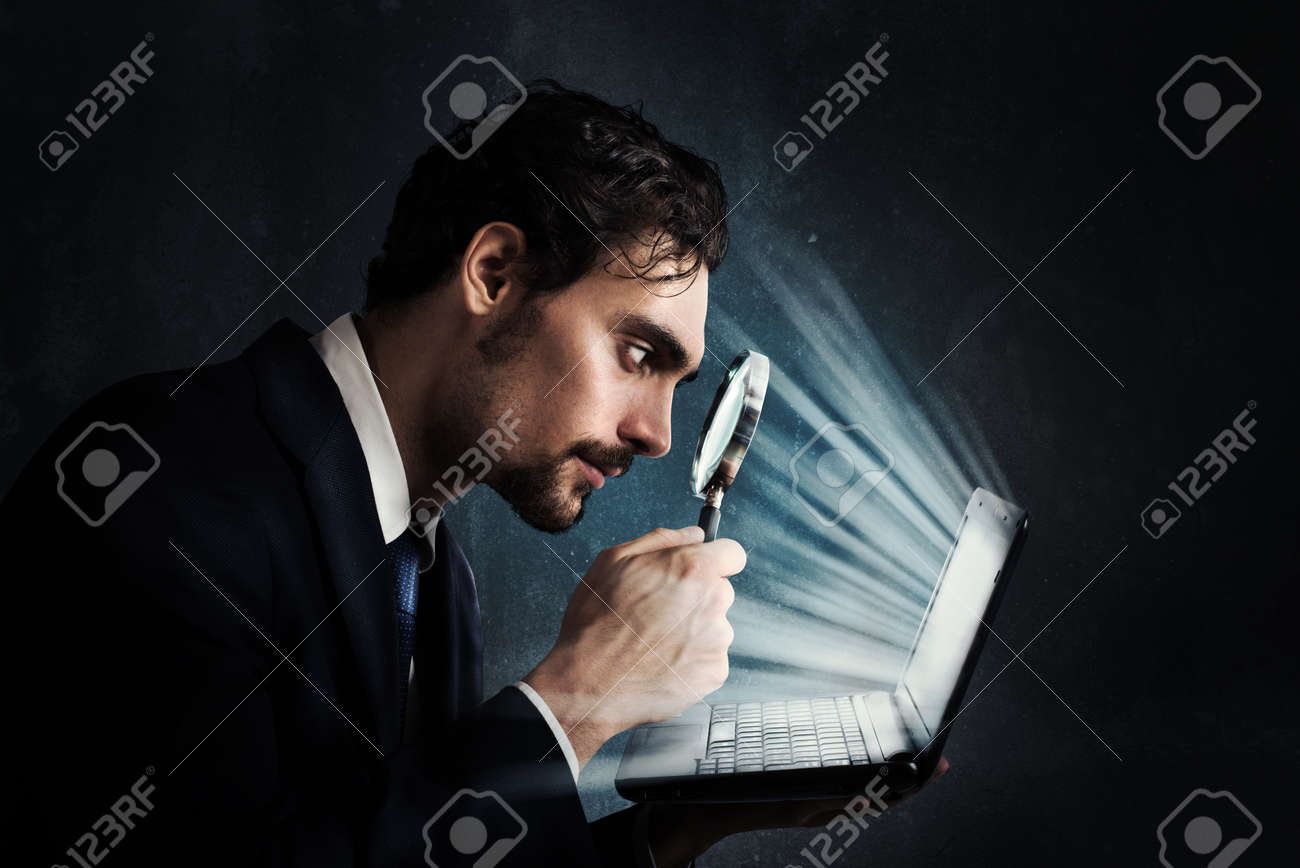 Businessman look with magnifying glass at the computer screen Standard-Bild - 64288859