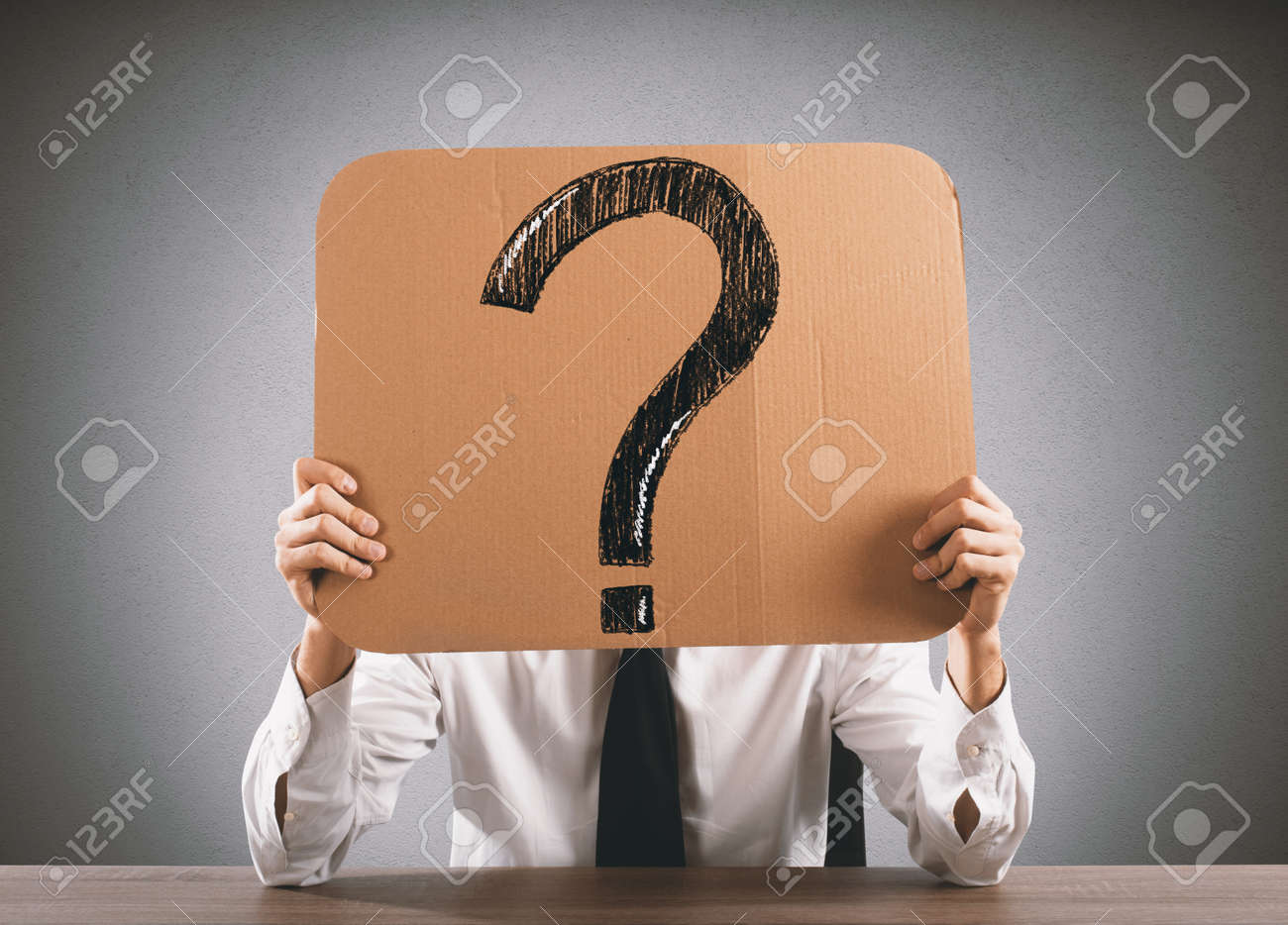 Businessman in the office holds a cardboard with big question mark Standard-Bild - 64803715