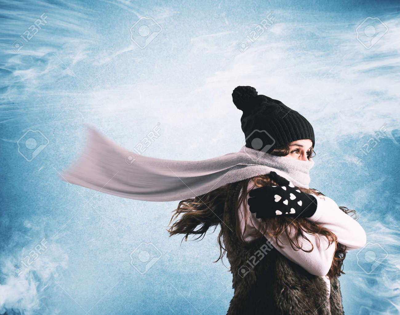 Woman with woolen scarf and hat trying to shelter from the winter cold Standard-Bild - 66762450