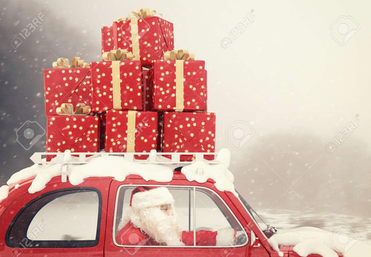 Santa Claus drives a red car full of Christmas present Standard-Bild - 66792349