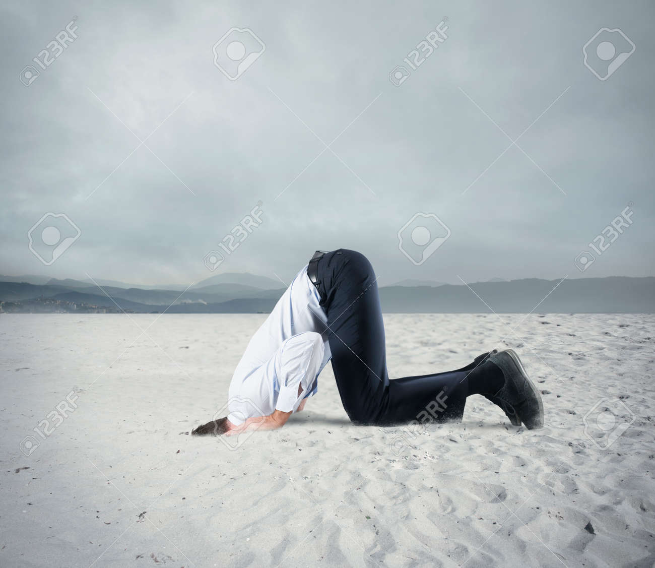 Afraid businessman hide his head under the ground like an ostrich. Fear of crisis concept - 67428261