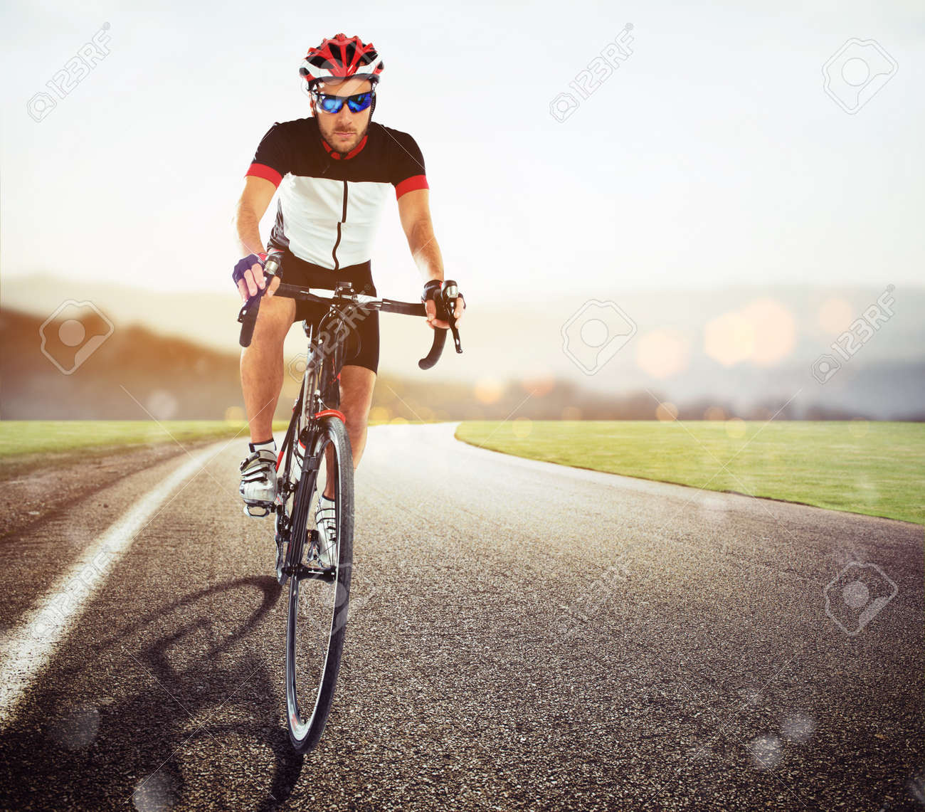 Front view of a road cyclist in uniform during a race at sunset - 82659592