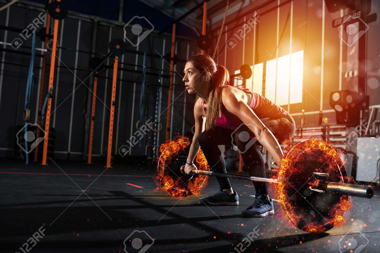 Athletic girl works out at the gym with a fiery barbell - 94766416