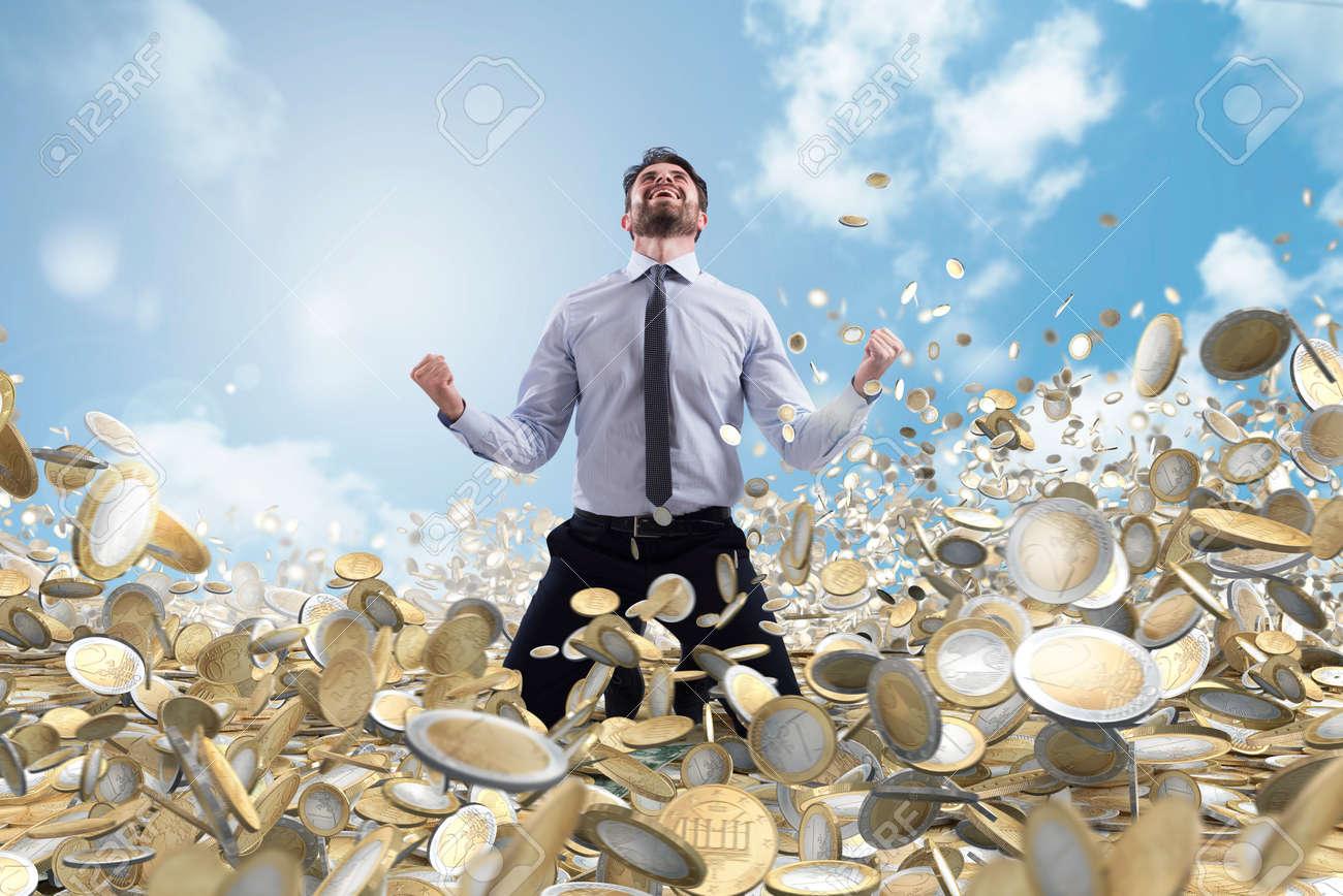 Businessman exults over a lot of money coins - 116758226