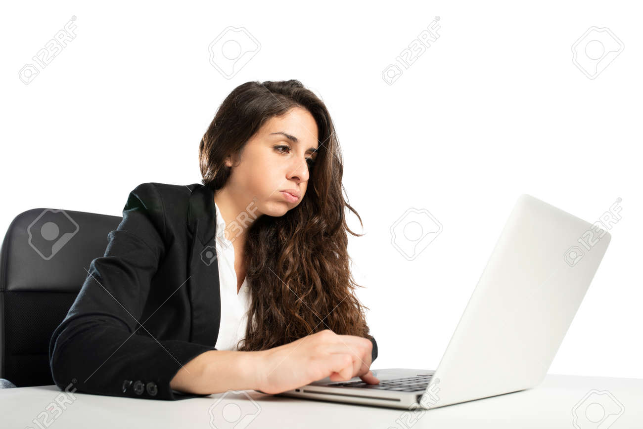 Bored woman snorts in the office while working on the laptop - 120561851