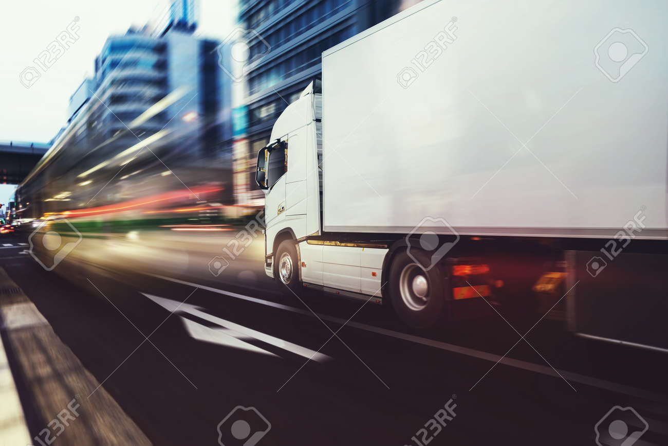 White truck moving fast on the road in a modern city with light effect - 120888190