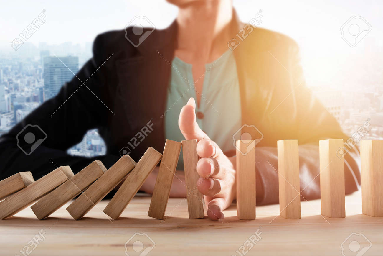 Businesswoman stops a chain fall like domino game. Concept of preventing crisis and failure in business. - 122367679