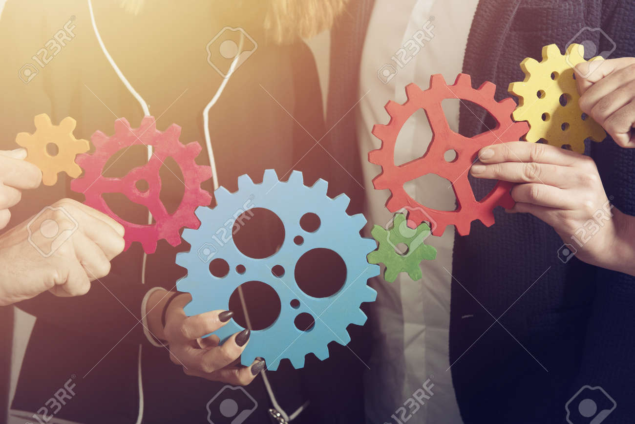 Business team connect pieces of gears. Teamwork, partnership and integration concept - 127025411