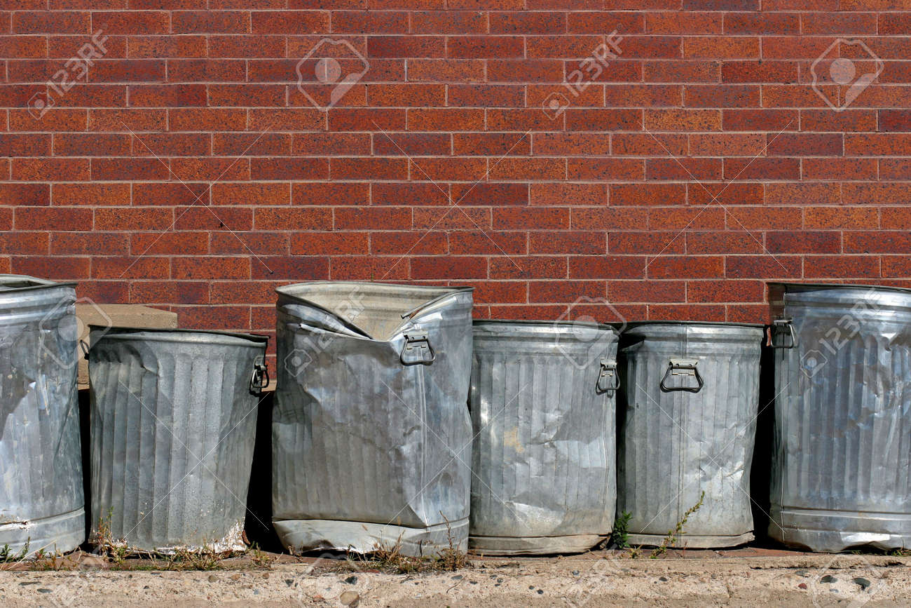 line of metal trash cans against a red brick wall stock photo