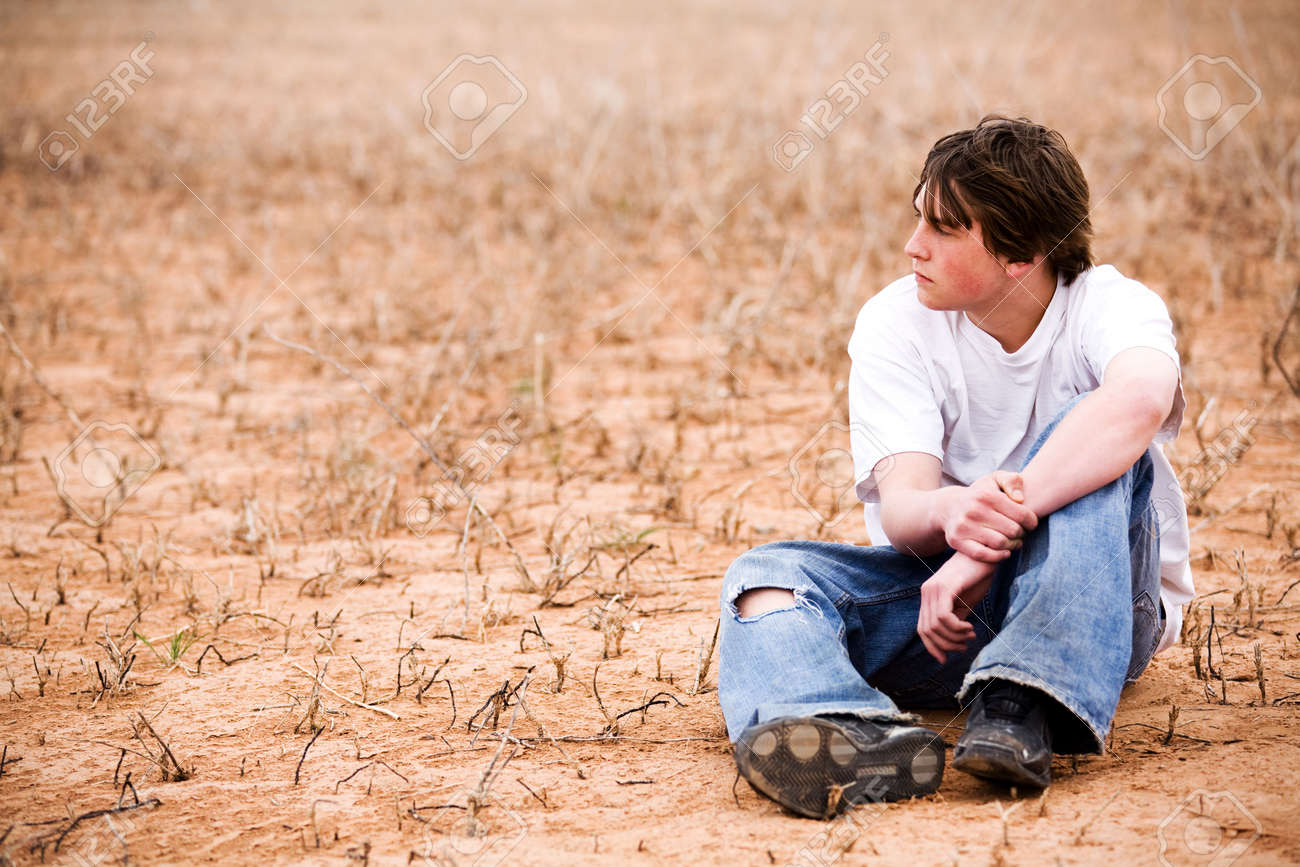 teenager sitting outdoors in wilderness area, dry lakebed among the weeds Stock Photo - 3008336