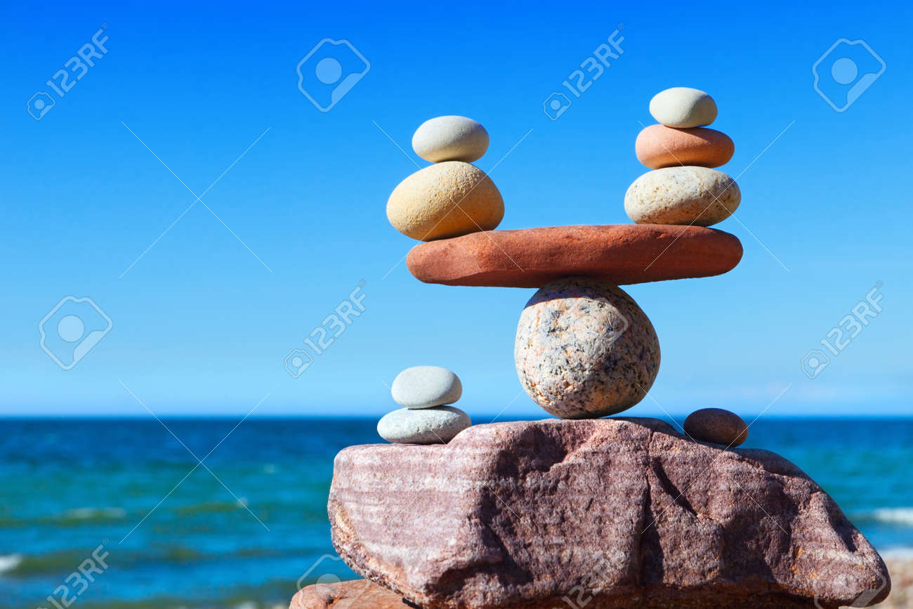 Symbolic scales of stones against the background of the sea and blue sky. Concept of harmony and balance. Pros and cons concept - 81132373