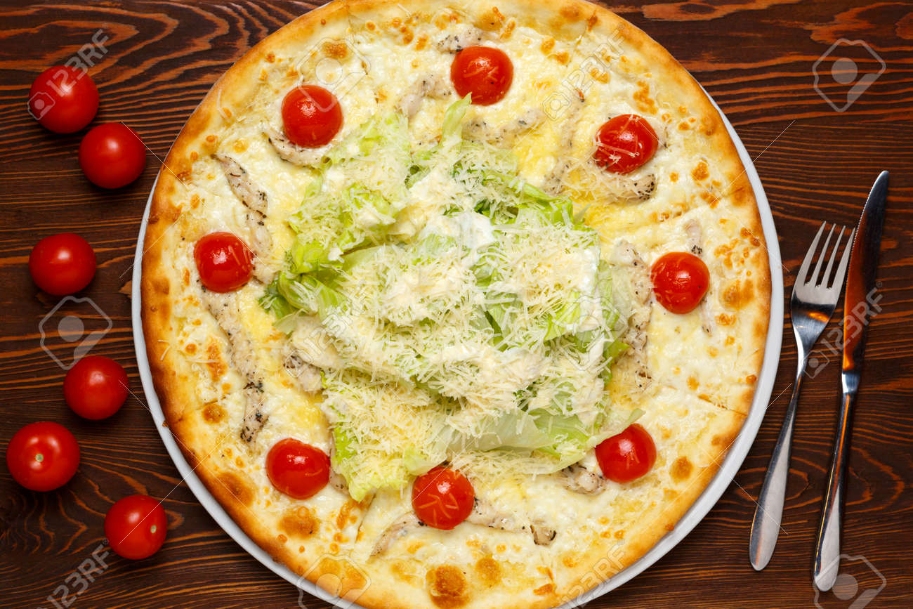 """Pizza with chicken, cheese, herbs and tomatoes """"Caesar"""" on a dark wooden table with a knife and fork. Top view - 158524259"""