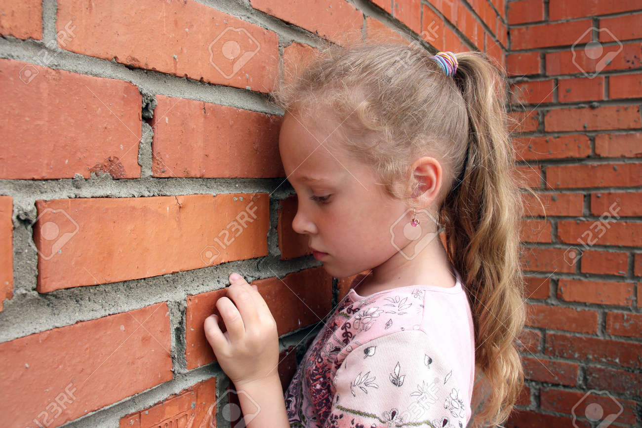 sad little girl on the background of an old brick wall Stock Photo - 16733275