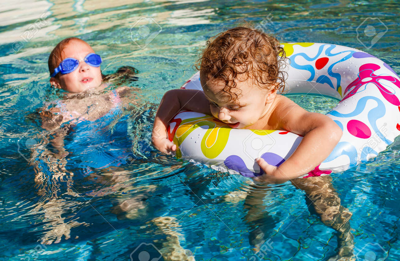 girl and little boy playing in the pool Stock Photo - 16792575