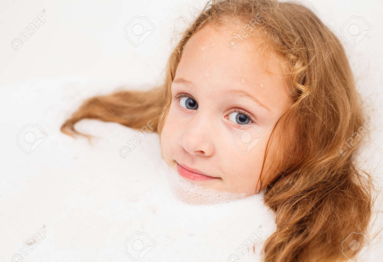 Cute eight year old girl taking a relaxing bath with foam. The symbol of purity and hygiene education. Stock Photo - 16803040