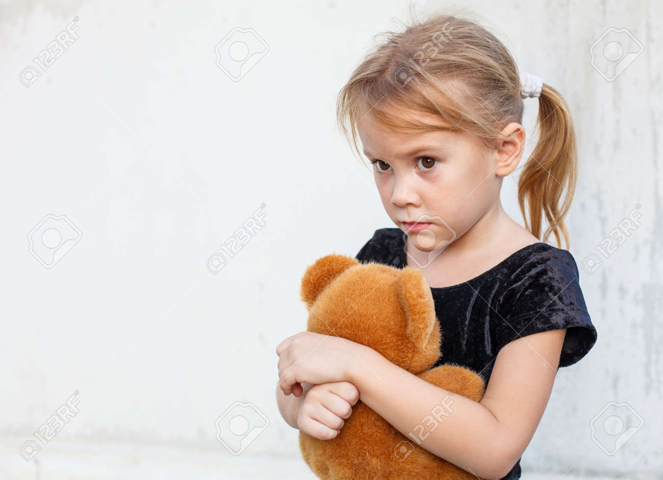 littl nude kids scared child: sad little girl on background the wall with toy