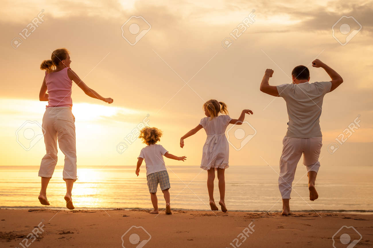 Happy beautiful family dancing on the  beach on the  dawn time Stock Photo - 24385867