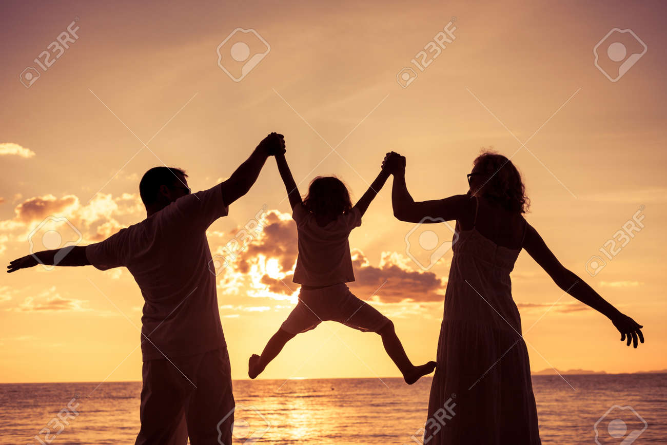 Silhouette of happy family who playing on the beach at the sunset time. Concept of friendly family. Stock Photo - 44376962