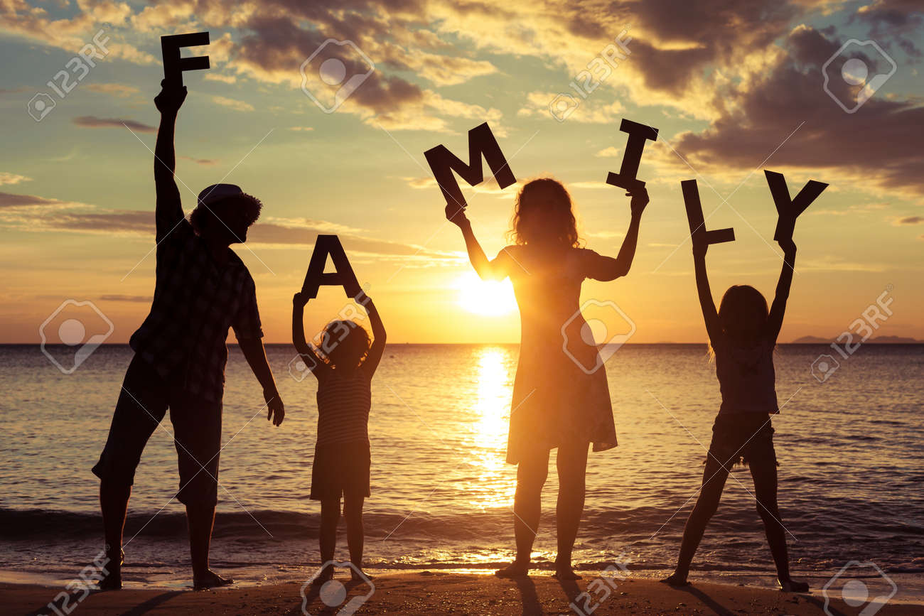 Happy family standing on the beach at the sunset time. They keep the letters forming