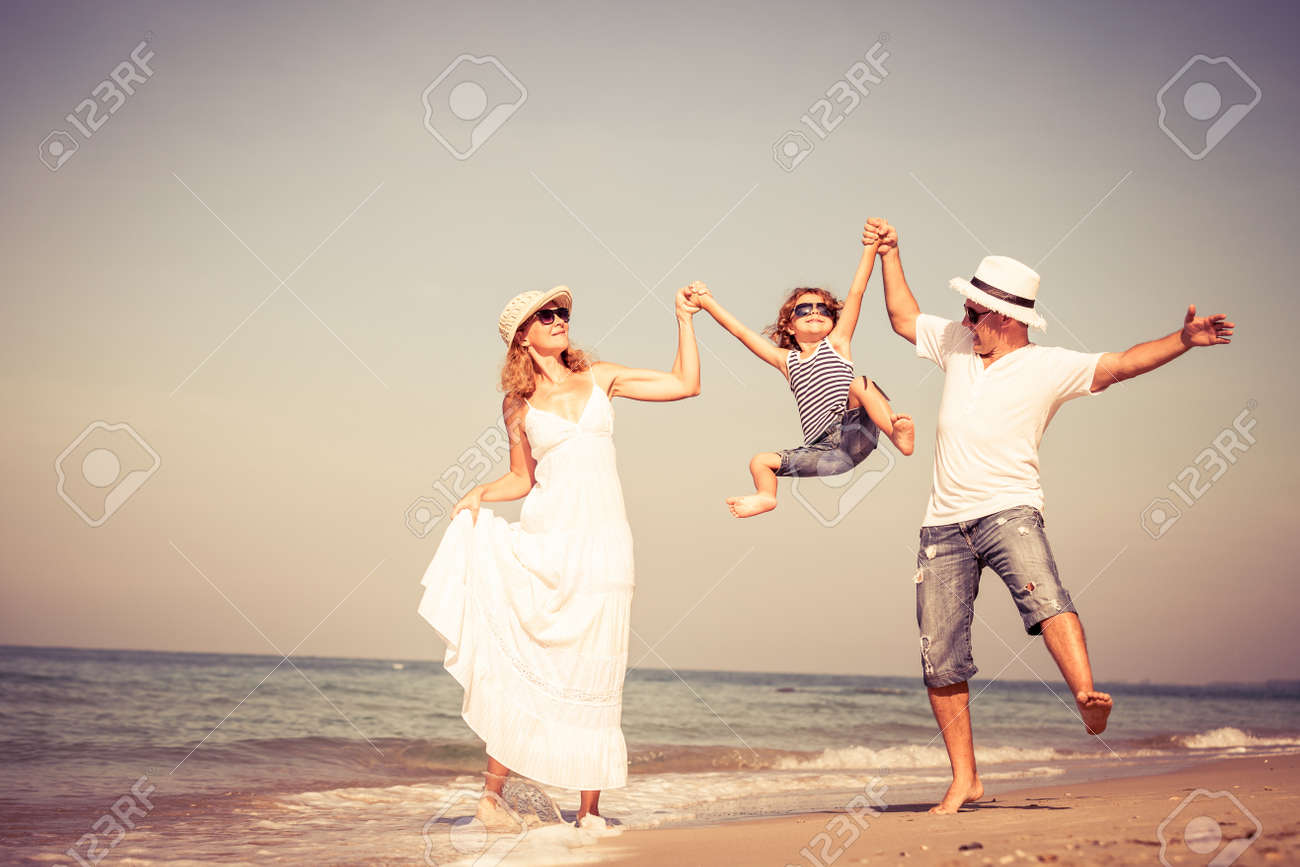 Happy family walking on the beach at the day time. Concept of friendly family. Stock Photo - 44833116