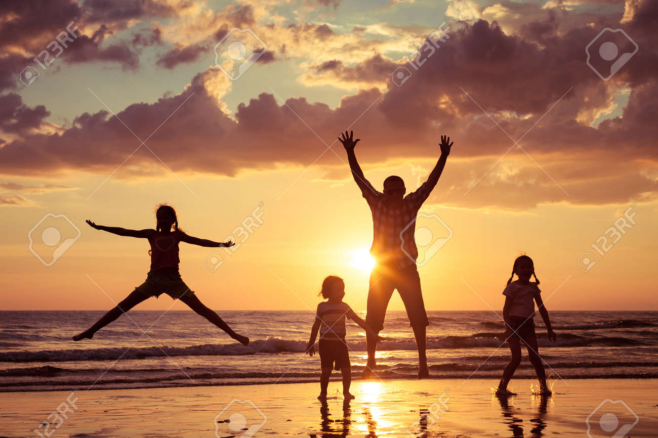 Father and children playing on the beach at the sunset time. Concept of friendly family. - 46432387