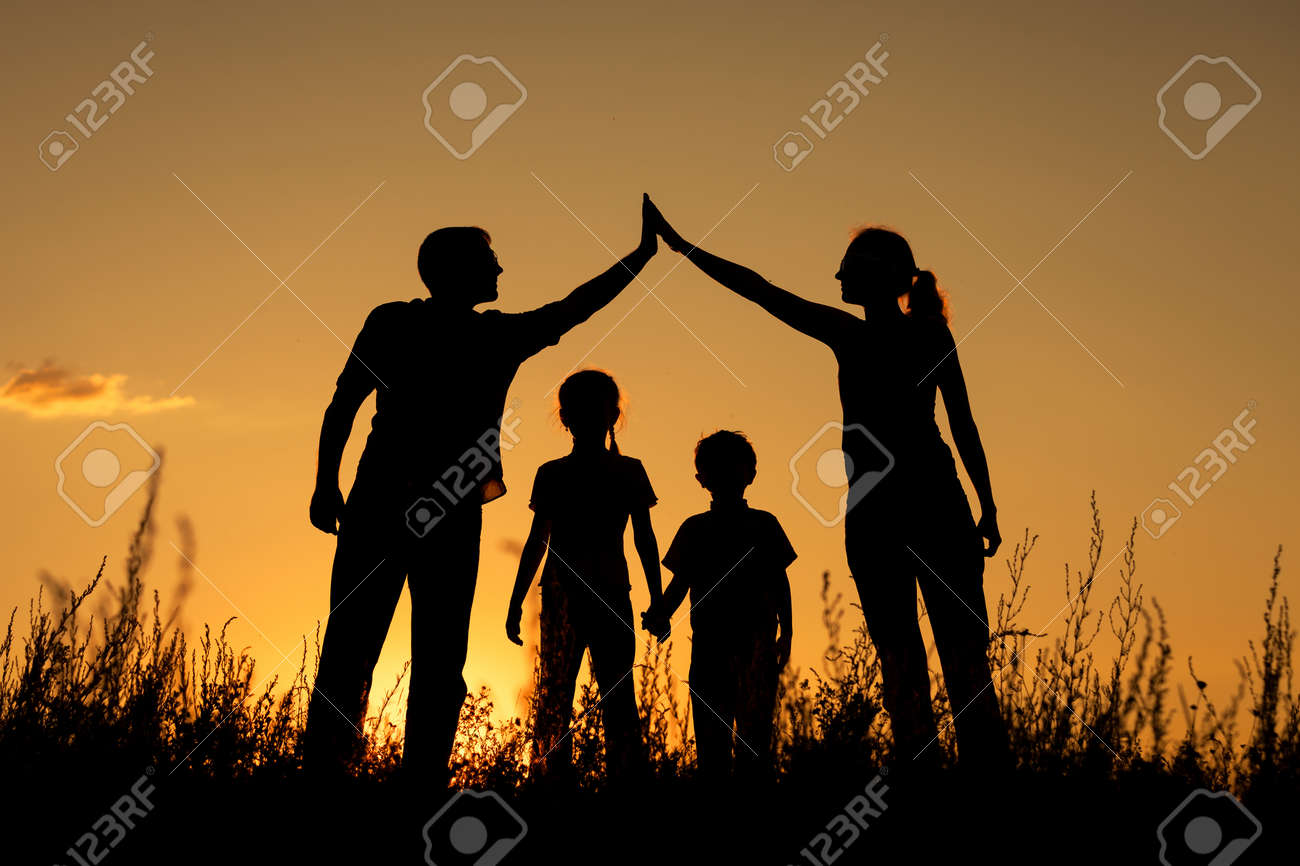 Happy family standing in the park at the sunset time.  Concept of friendly family. Stock Photo - 47223108