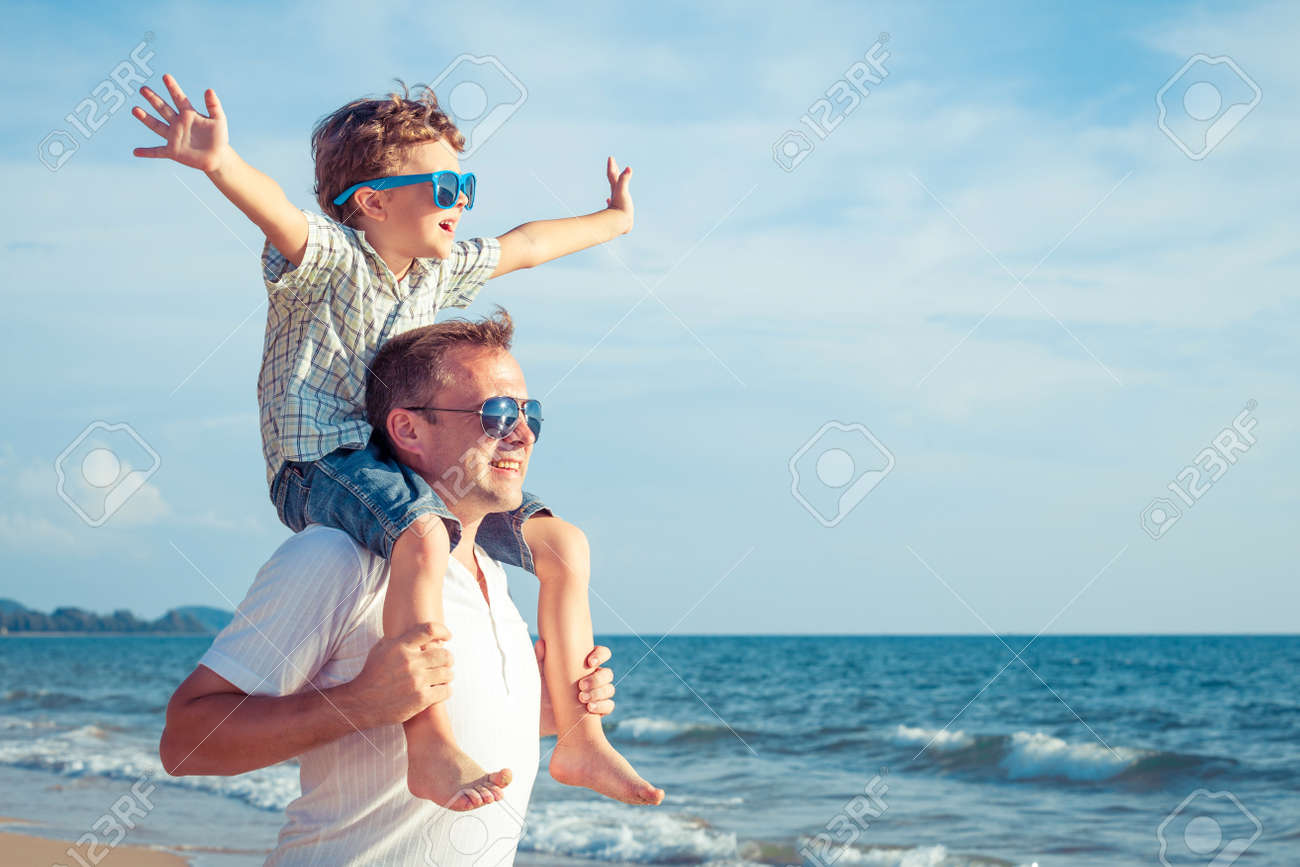 Father and son playing on the beach at the day time. Concept of friendly family. - 51580812