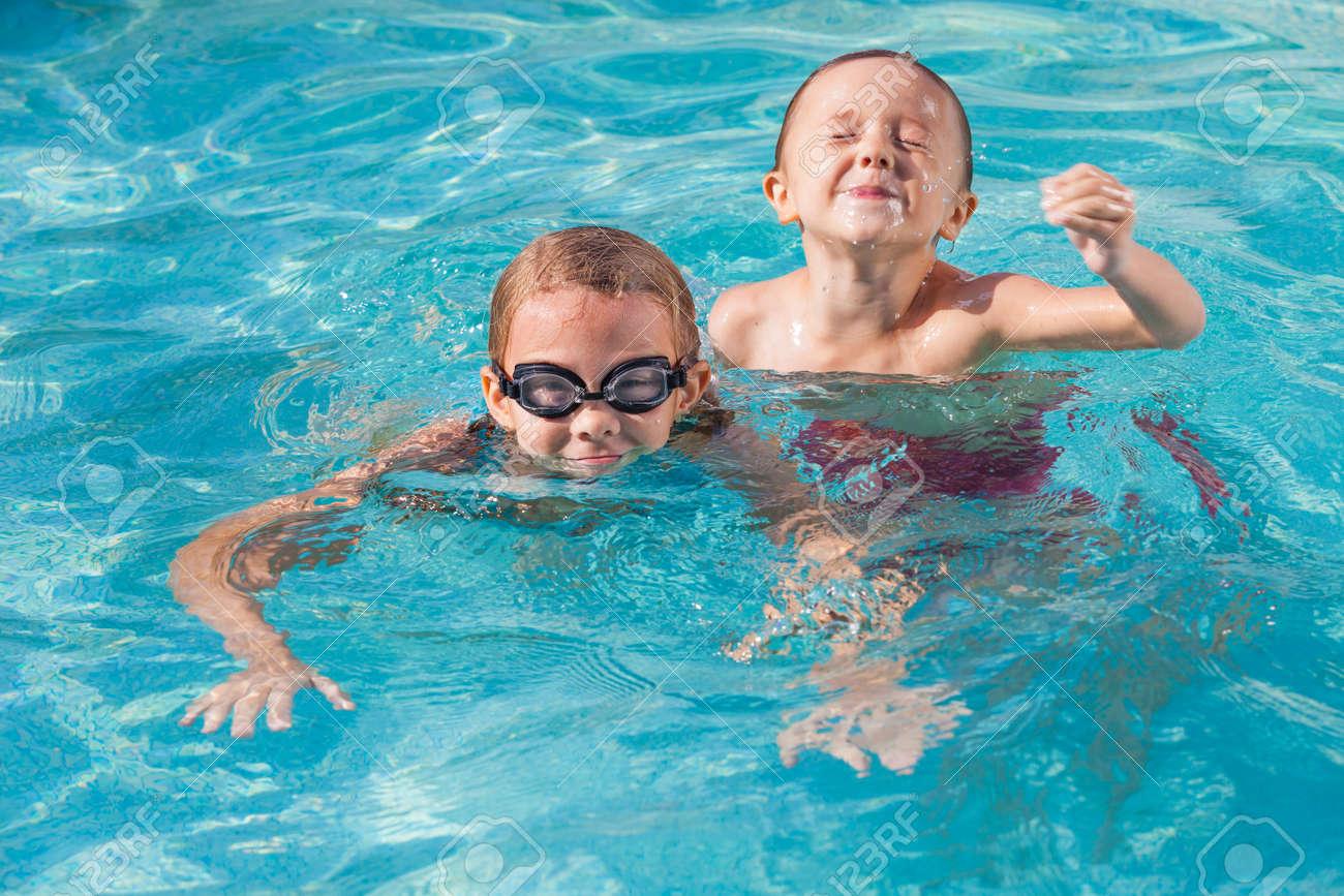 161fcf9b40aca Standard-Bild - Zwei glückliche Kinder, die auf dem Schwimmbad am Tag Zeit  zu spielen. Menschen Spaß im Freien. Konzept der freundlichen Geschwister.
