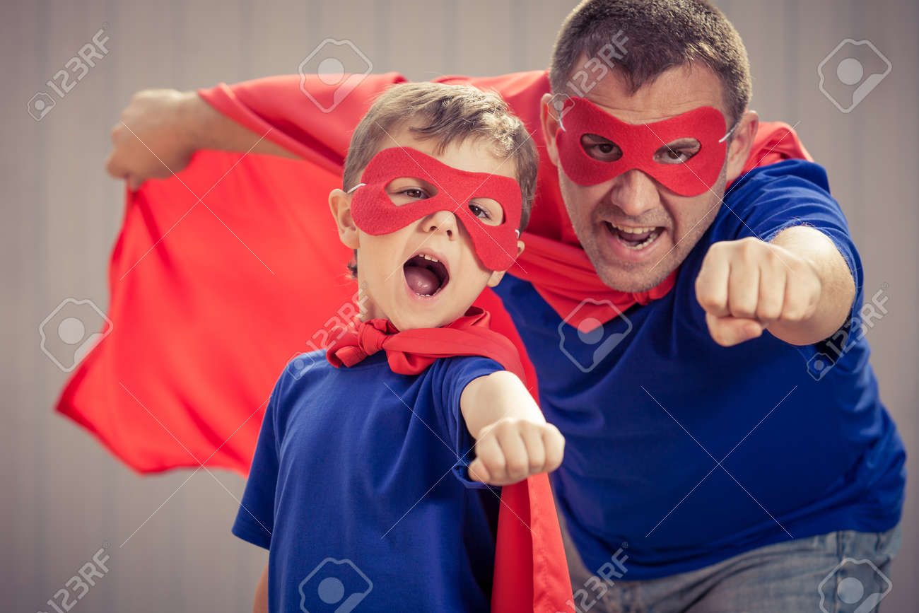 Father and son playing superhero at the day time. People having fun outdoors. Concept of friendly family. - 64435624