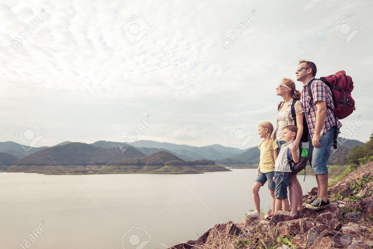 Happy family standing near the lake at the day time. Concept of friendly family. - 142834748