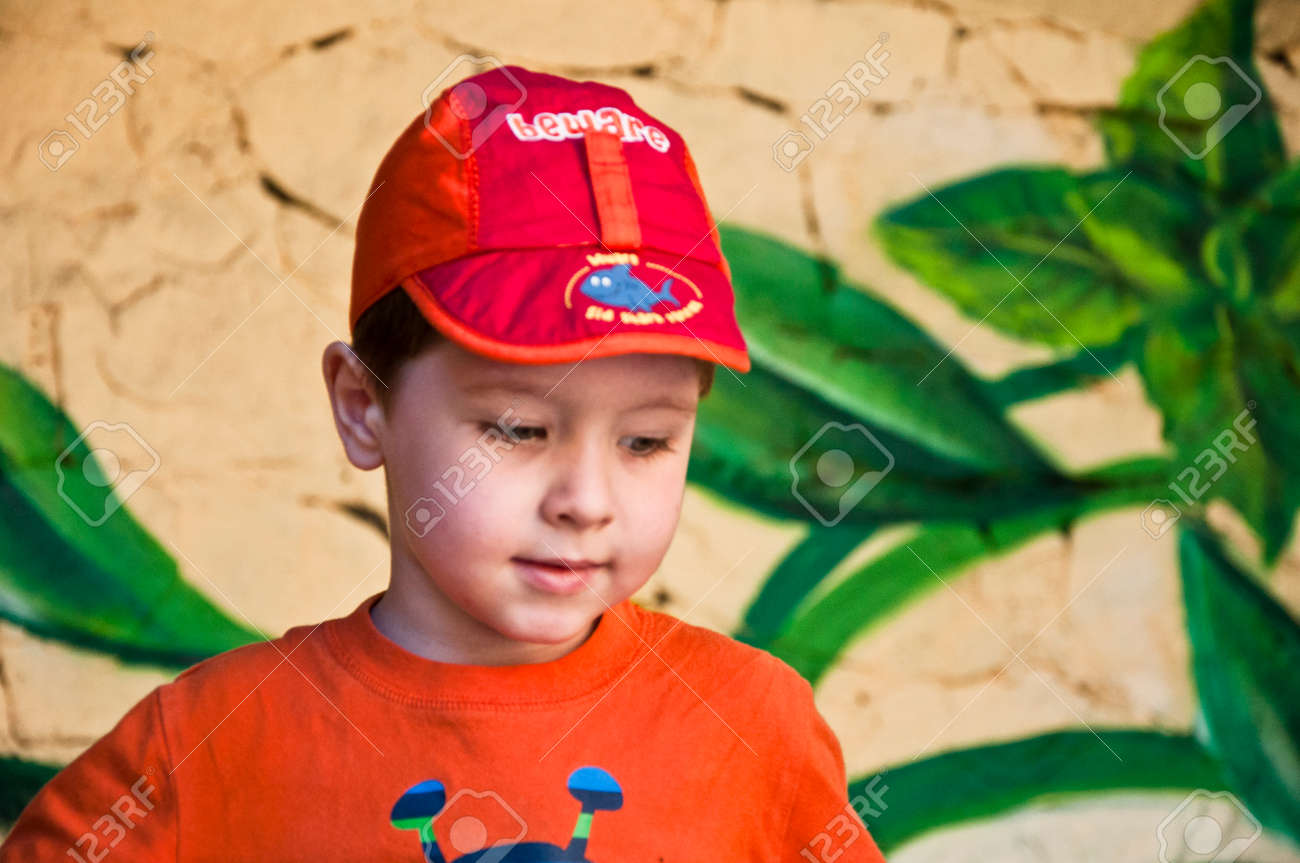cute small baby boy or emotional child in red cap and orange shirt outdoor  on paint aa83fa1e2bc
