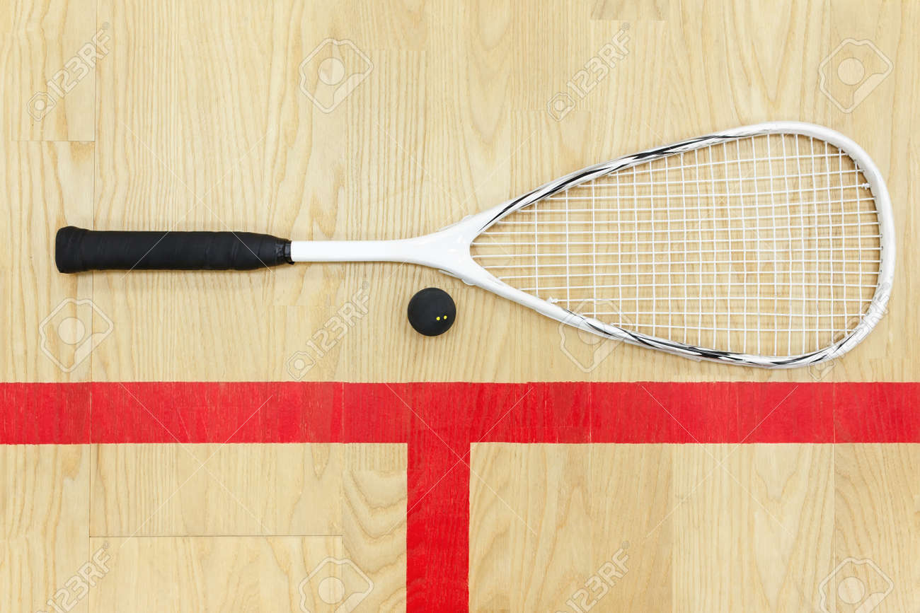 white squash racket and ball on the wooden floor top view. Racquetball equipment on the court near red line - 76549541