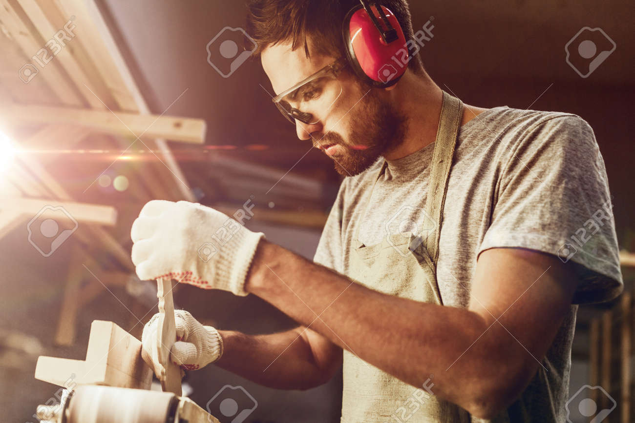 Bearded craftsman shaping wooden detail on belt sander - 115953469