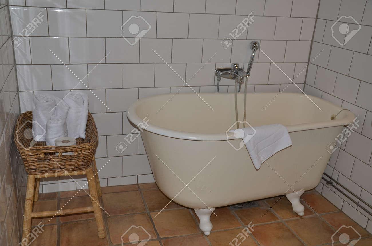 Ancien bain dans une salle de bains avec carrelage blanc banque d ...
