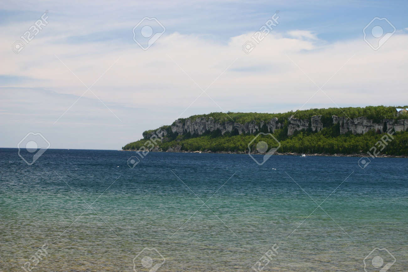 A tree cloaked headland, with high stone cliffs juts into the crystalline, blue waters of Georgian Bay. Taken from the shoreline in village of Lion's Head, Ontario. Stock Photo - 3382717