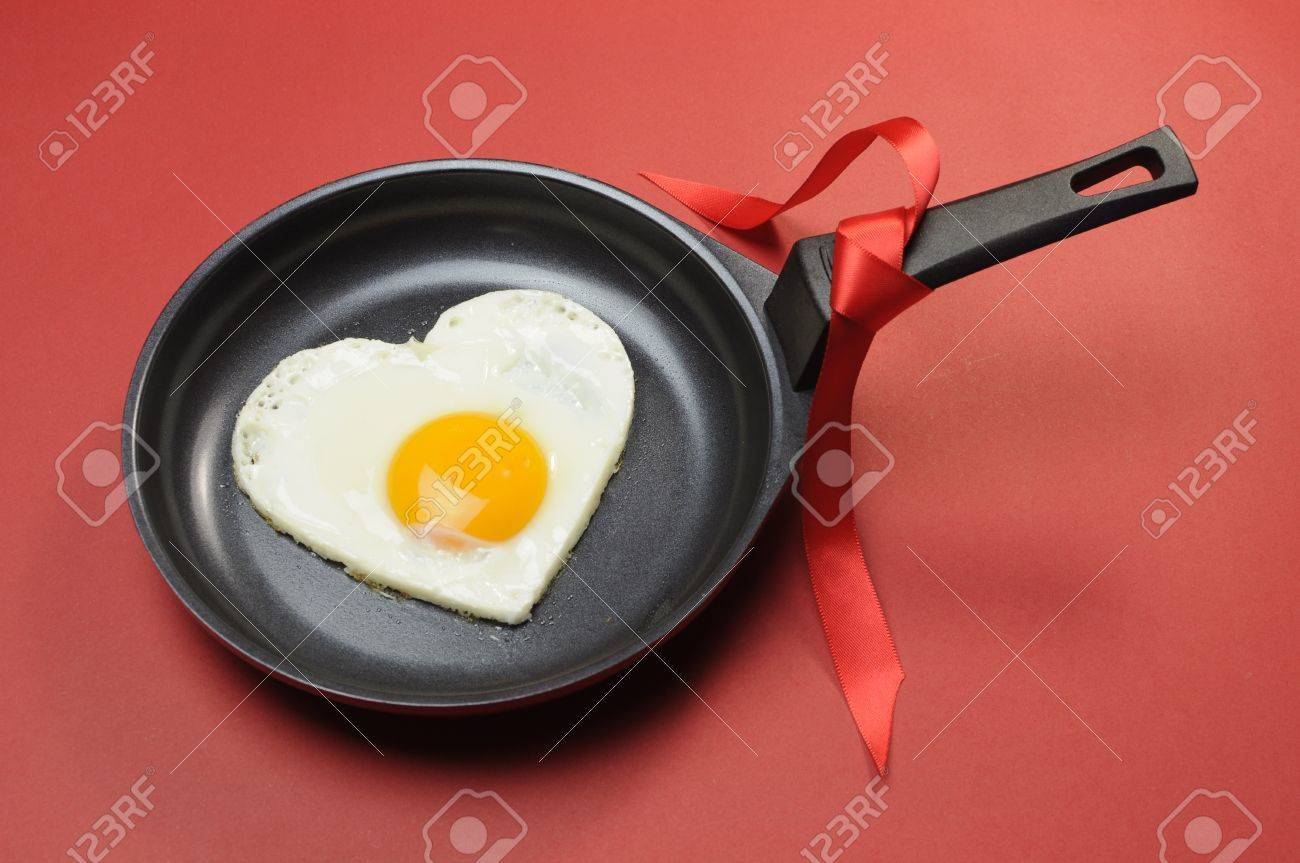 Red theme Valentine breakfast egg in fry pan with love on red background Stock Photo - 17746687