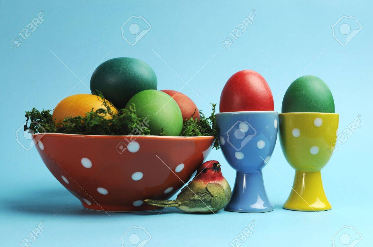 Bright and cheerful Happy Easter still life with rainbow color eggs in orange polka dot bowl and egg cups against a blue background Stock Photo - 17746782