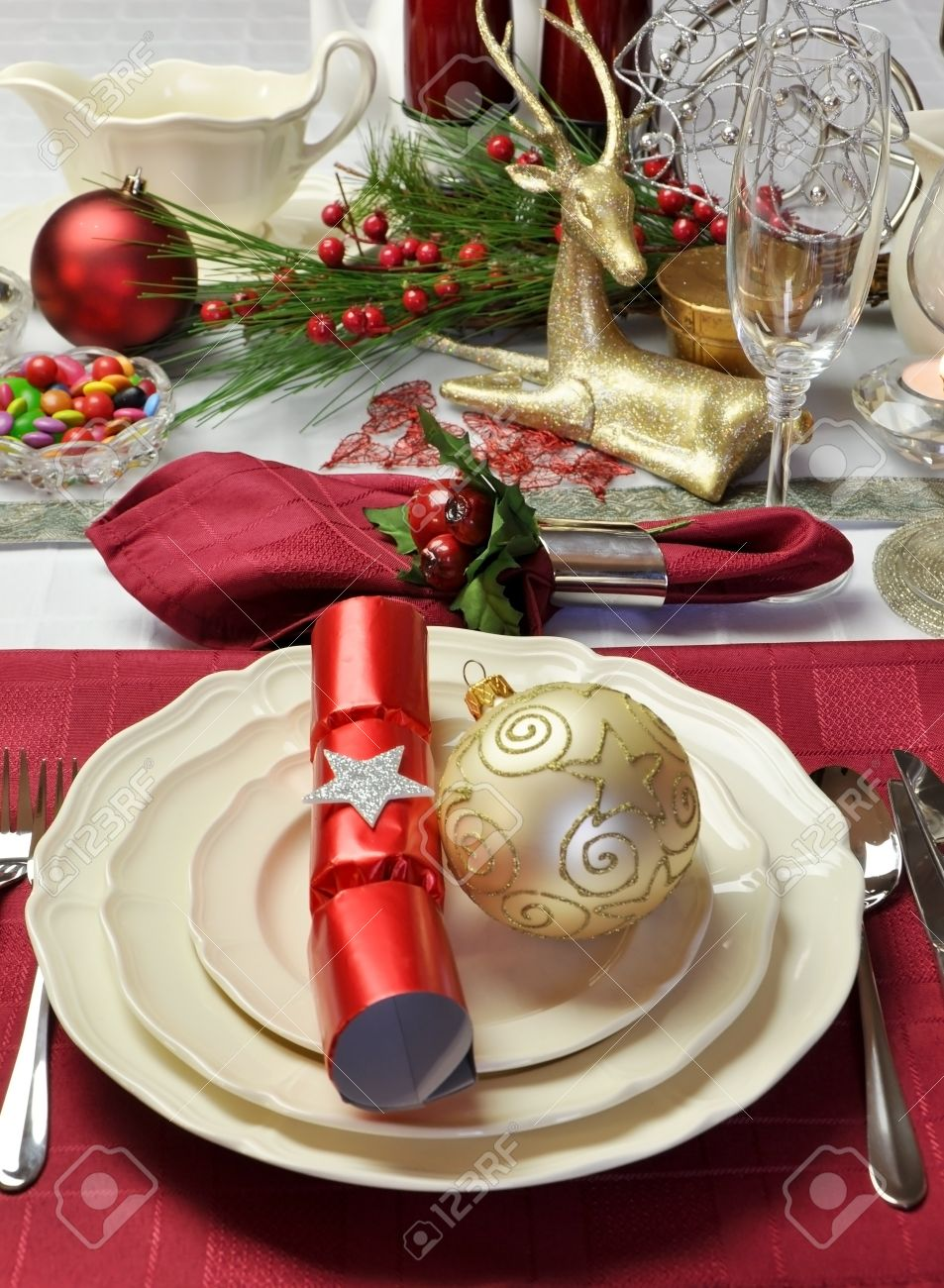 Modern and stylish Christmas dinner table setting including plates glasses and placemats bon bons & Modern and stylish Christmas dinner table setting including plates..