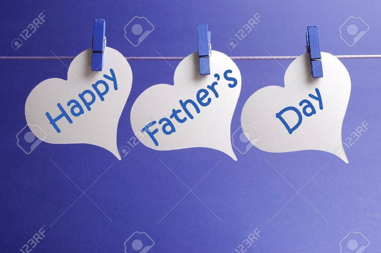 happy fathers day message written on white heart shape tags hanging from blue pegs on a