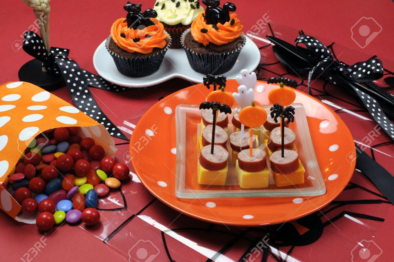samedi 31 octobre  19056975-Bonne-table-de-f-te-Halloween-avec-un-verre-squelette-petits-g-teaux-des-sucettes-de-bonbons-et-de-l-Banque-d'images