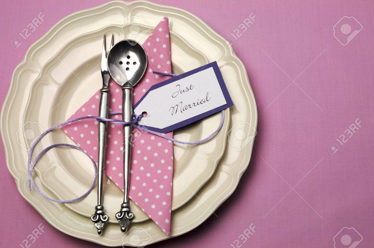 pale pink theme wedding table place setting with polka dot napkin and antuque silverware with just