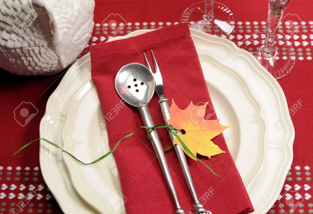Red and white theme festive fine dining table setting with autumn fall leaf decoration, crystal wine glass, and turkey tureen pot, for Thanksgiving or Christmas place setting. Stock Photo - 23831787