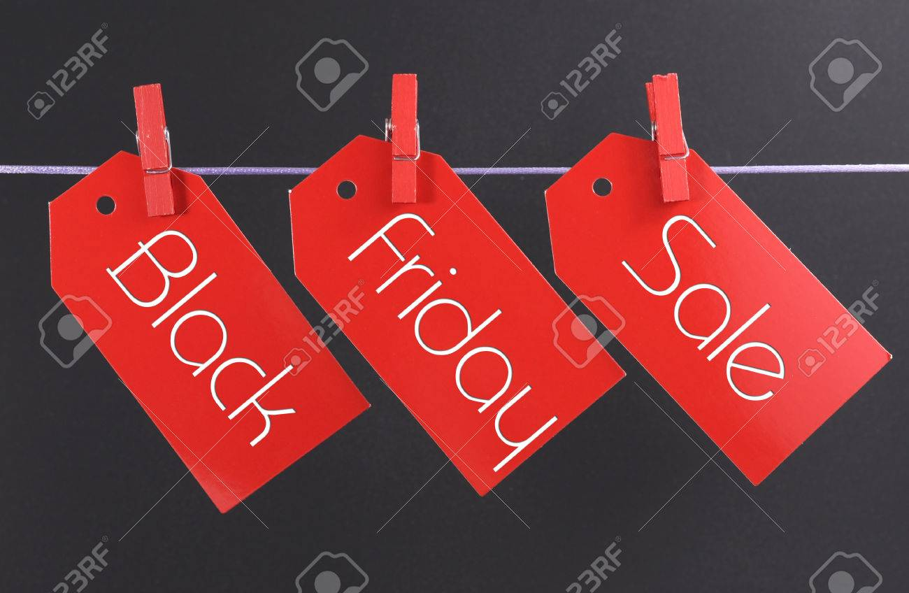 Black Friday shopping sale concept with message written across red ticket sale tags hanging from pegs on a line - 23831792