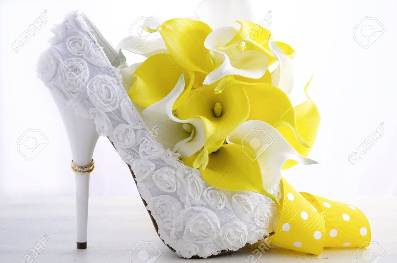 Wedding day concept with rings on heel of beautiful white floral stock photo wedding day concept with rings on heel of beautiful white floral bridal stiletto shoes with bouquet on white shabby chic wood table mightylinksfo