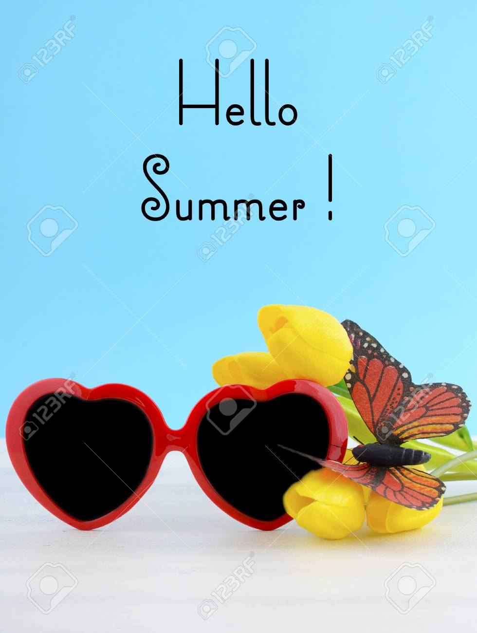 4a55cb4492 Stock Photo - Summer Is Here concept with red heart shape sunglasses with  butterfly on yellow flowers on white wood table and sky blue background.