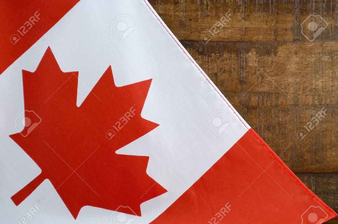 canadian red and white maple leaf flag against dark wood rustic