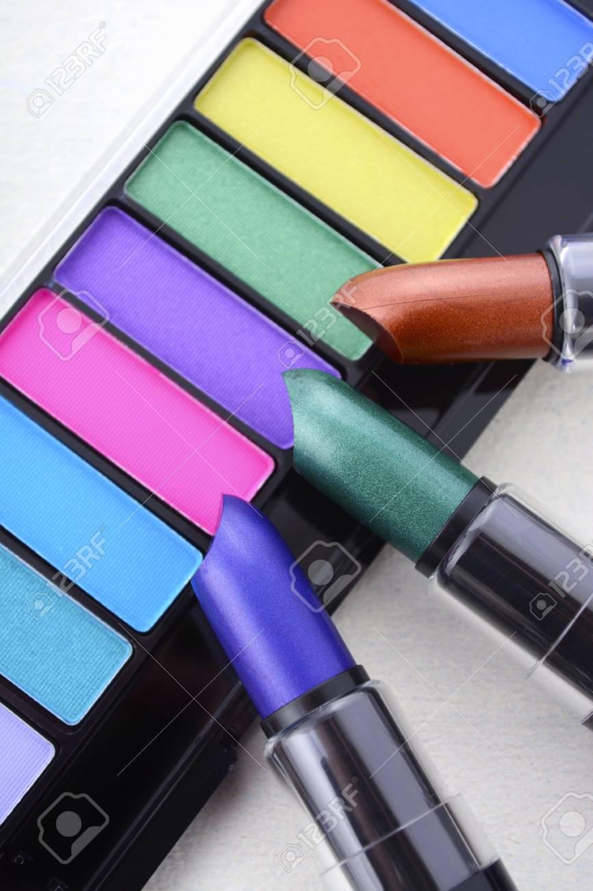 Maquillage moderne vif, lumineux gamme de couleurs de fard à paupières avec des rouges à lèvres vert, violet et blanc bronze sur table en bois fond.
